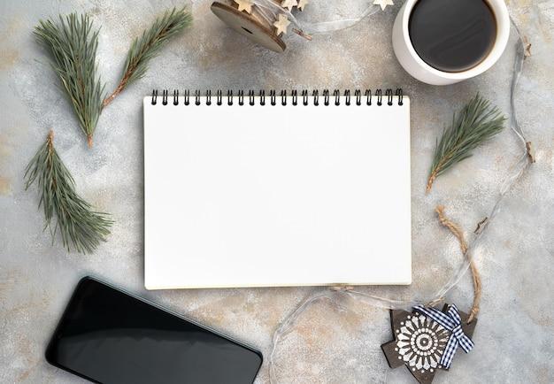 Bloc-notes, branches de pin, café et téléphone sur une surface grise