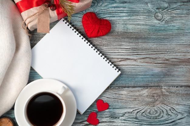 Bloc-notes avec café et cadeau dans une ambiance chaleureuse et romantique.