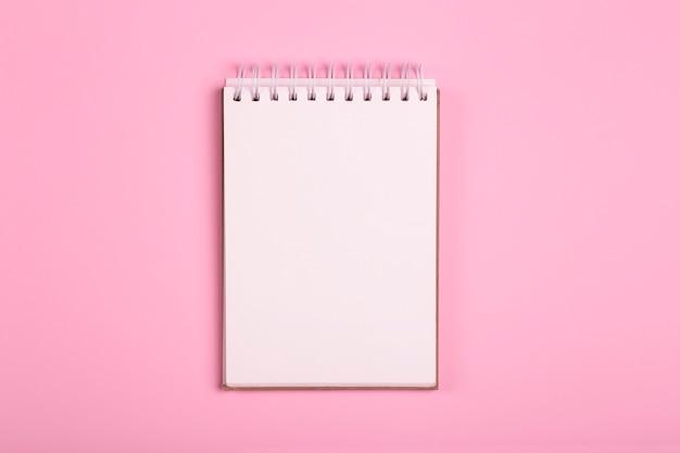 Bloc-notes ou cahier vierge sur fond rose. espace pour les inscriptions et les notes
