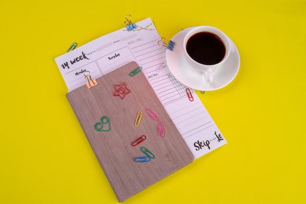 Bloc-notes avec calendrier et tasse de café.