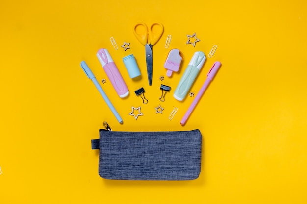 Bloc-notes de concept de retour à l'école, trousse, papeterie et fournitures scolaires. vue de dessus du mur jaune de la surface horizontale
