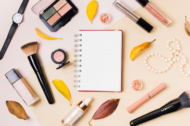 Bloc-notes avec des cosmétiques de maquillage sur un bureau lumineux