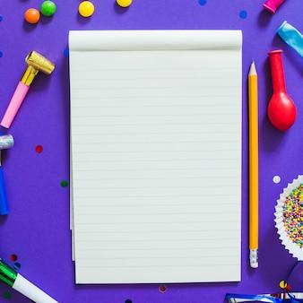 Bloc-notes avec crayon dans des objets de fête
