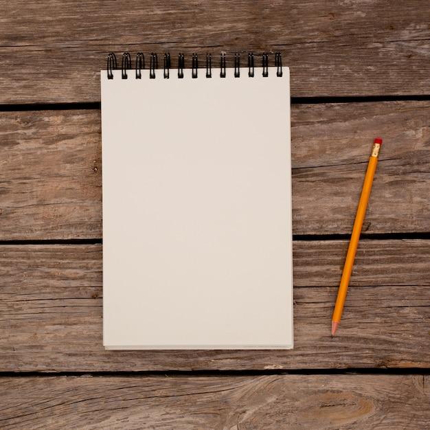 Bloc-notes avec un crayon sur fond de planche de bois