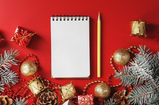 Bloc-notes et crayon pour écrire des souhaits et des cadeaux pour le nouvel an et noël autour du sapin de noël