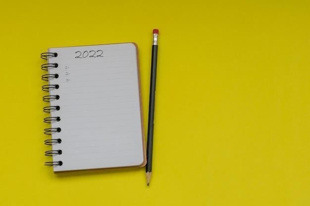 Bloc-notes avec crayon pour faire la liste des objectifs et des nombres 2022 fermer les plans et objectifs pour 2022