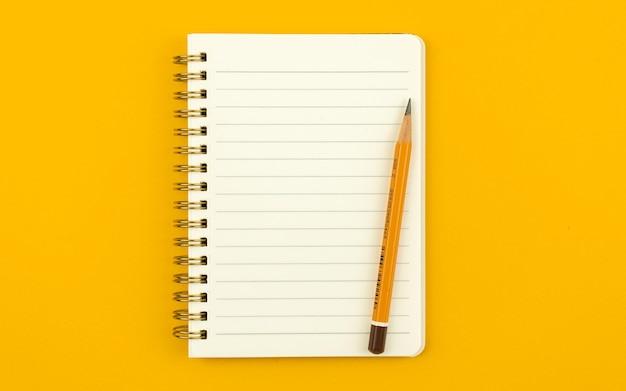 Bloc-notes avec un crayon sur une table et un arrière-plan orange coloré et lumineux, photo vue de dessus avec espace de copie