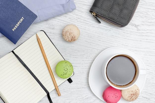 Bloc-notes avec un crayon, une tasse à café, des macarons et un passeport. concept de voyage