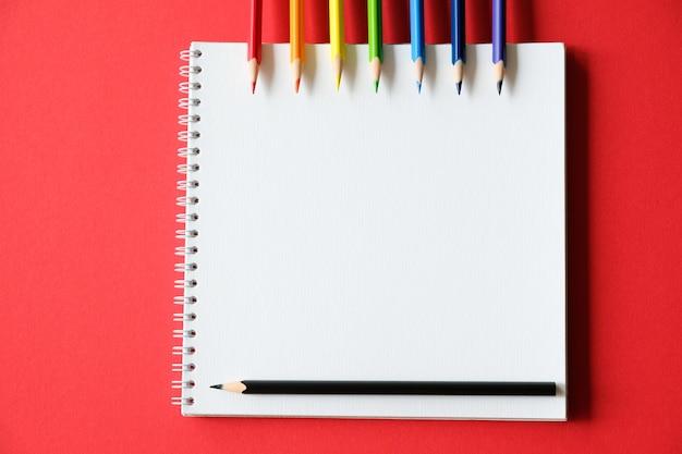 Bloc-notes et crayons de couleur sur la table