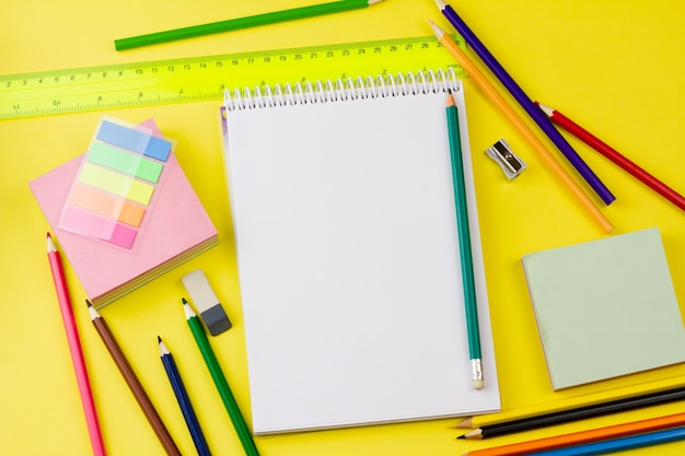 Bloc-notes avec des crayons sur fond jaune.