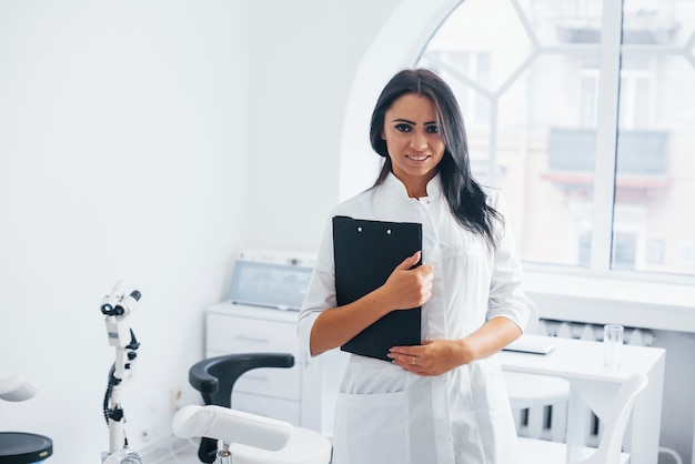 Avec bloc-notes dans les mains. une femme médecin brune se tient dans un bureau moderne et regarde la caméra.