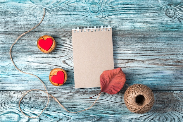 Bloc-notes et deux coeurs rouges sur fond gris-bleu en bois.
