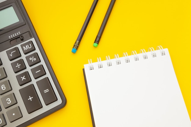 Bloc-notes avec deux crayons et une calculatrice sur jaune