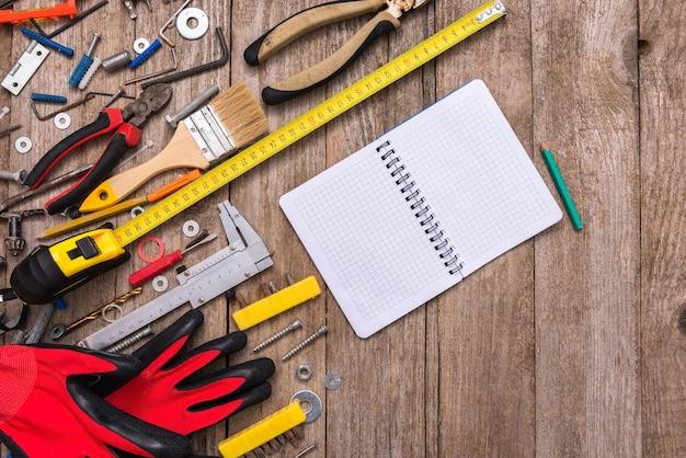 Bloc-notes entouré d'outils poussiéreux sur un vieux fond en bois.