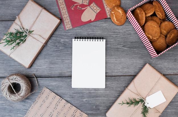 Bloc-notes entre cadeaux, biscuits dans une boîte, cartes postales et canette de fil