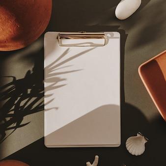 Bloc-notes de feuille de papier vierge avec espace de copie, pierres, coquillages, corail, bougie, pot d'argile dans les ombres de la lumière du soleil floral sur vert foncé