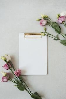 Bloc-notes de feuille de papier vierge avec des fleurs de roses sur gris neutre