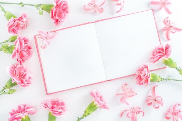 Bloc-notes et fleurs sur blanc
