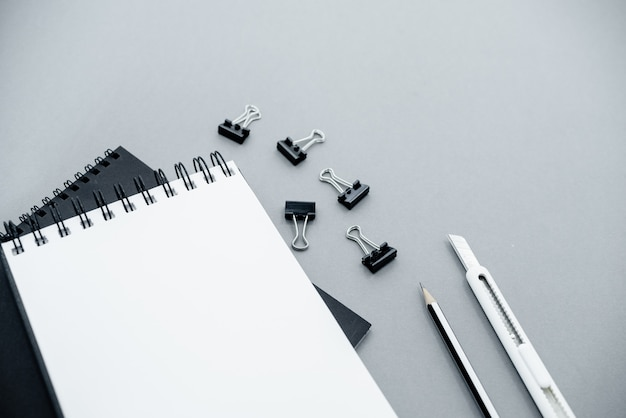 Bloc-notes sur un fond abstrait gris avec espace copie, style minimal.