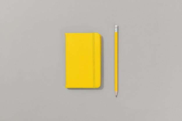 Bloc-notes jaune avec un crayon sur fond gris