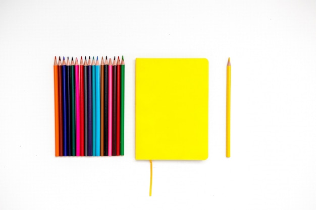 Bloc-notes jaune avec des crayons de couleur sur fond blanc