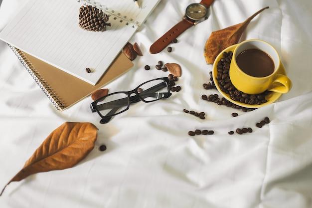 Bloc-notes lettre tasse de café et un livre avec une couverture sur un textile blanc au lit.