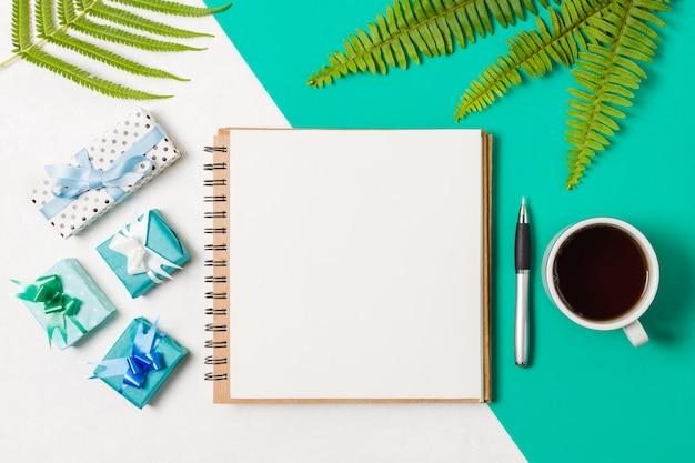 Bloc-notes noir; cadeaux avec une tasse de café disposées sur un fond blanc et turquoise