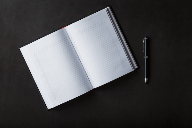 Bloc-notes noir avec un stylo noir sur fond noir. vue de dessus, concept minimaliste. espace libre.
