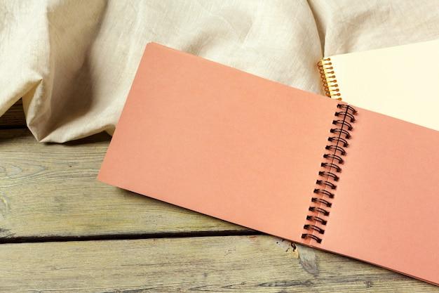 Bloc-notes ouvert blanc sur fond en bois avec un morceau de tissu
