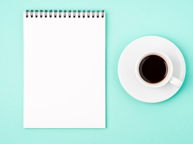 Bloc-notes ouvert avec une page blanche blanche pour écrire une idée ou une liste de choses à faire, tasse de café sur fond bleu