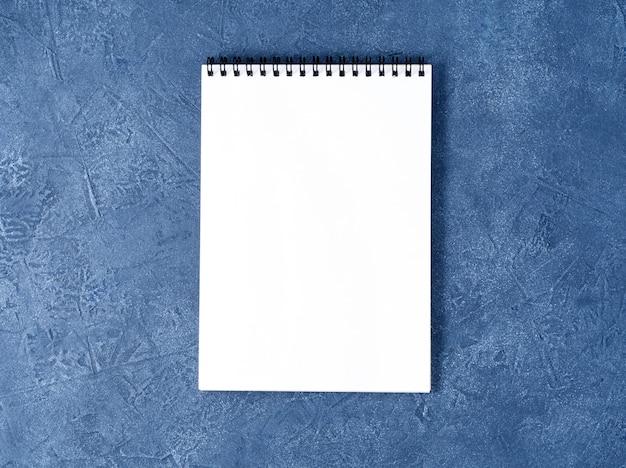 Le bloc-notes ouvert, une page blanche sur une table en pierre bleue foncée, vue de dessus