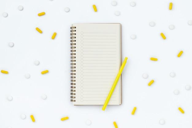 Bloc-notes ouvert et pilules dispersées sur tableau blanc
