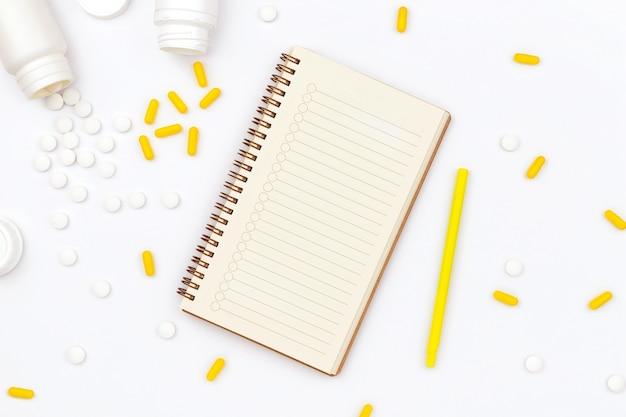 Bloc-notes ouvert et pilules éparpillées sur tableau blanc