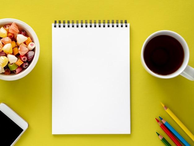 Bloc-notes ouvert en spirale avec une page blanche et propre, une tasse de thé, des caramels dans un bol, un crayon de couleur