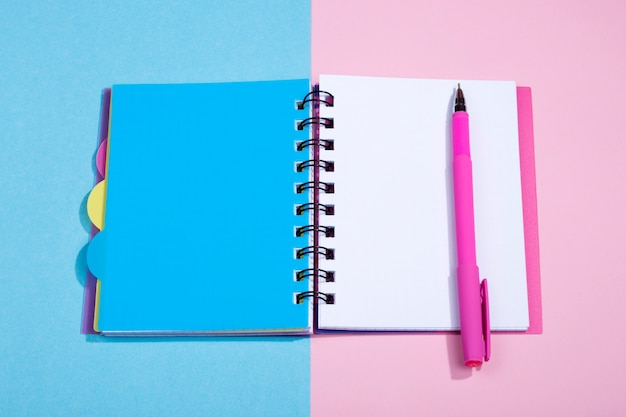 Bloc-notes ouvert et un stylo plume rose sur fond multicolore