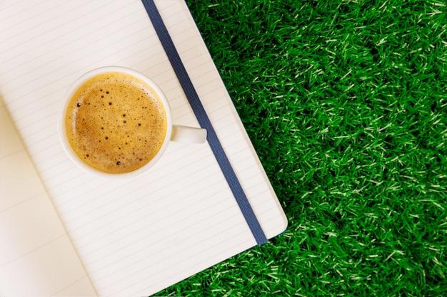 Bloc-notes ouvert vide et tasse de café expresso sur une herbe verte