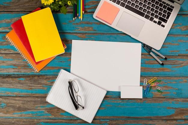 Bloc-notes, page blanche, lunettes, agendas, stylos, crayons de couleur, ordinateur portable et épingles à papier