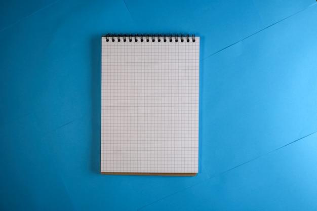 Bloc-notes avec des pages à carreaux à feuilles mobiles sur un fond de papier bleu pour le texte