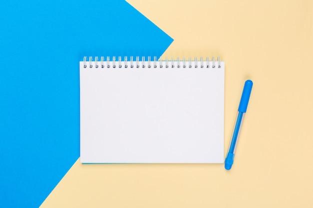 Bloc-notes papier blanc sur fond bicolore lumineux pour votre conception, vue de dessus