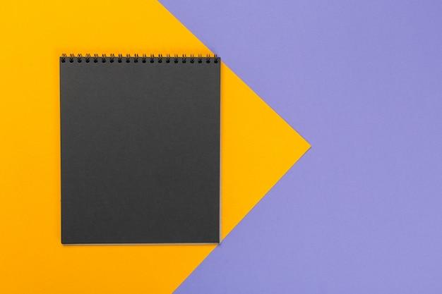 Bloc-notes de papier vierge sur fond bicolore brillant pour votre conception, vue de dessus