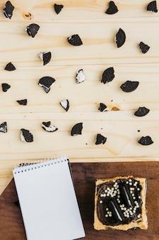 Bloc-notes avec pâtisserie près de morceaux de biscuits sur une table en bois