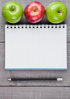 Bloc-notes avec des pommes saines comme idée de plan de régime sur planche de bois