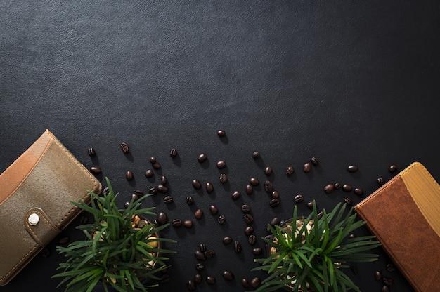 Le bloc-notes, les pots de fleurs et les grains de café sont placés sur le bureau, vue de dessus.