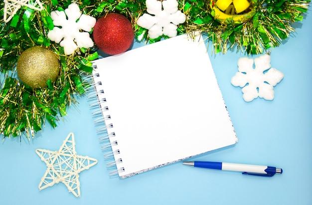 Un bloc-notes pour les notes avec un stylo et des décorations de noël fond bleu du nouvel an