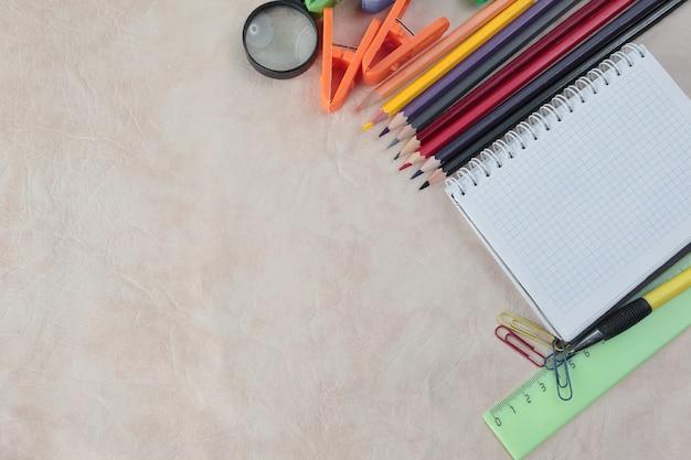 Bloc-notes pour prendre des notes et des fournitures scolaires sur un fond de papier .photo avec espace de copie.