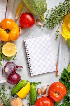 Bloc-notes pour votre recette avec des légumes, des herbes et des épices sur fond blanc. vue de dessus avec espace de copie. liste de courses, plan de régime. cahier avec stylo parmi différents légumes.