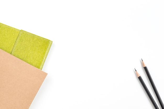 Bloc-notes recyclé de couleur verte et marron et deux crayons noirs sur fond blanc