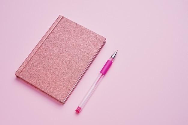 Bloc-notes rose avec un stylo sur fond rose pastel.