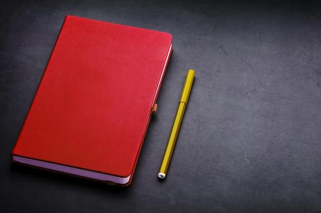 Bloc-notes rouge avec un marqueur sur fond noir, vue de dessus.