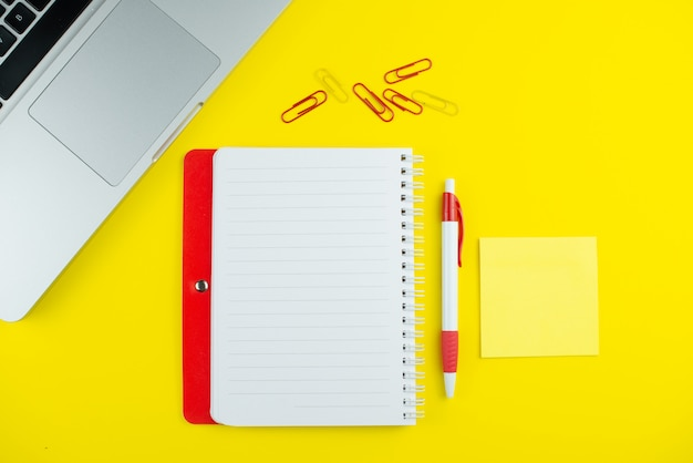 Bloc-notes rouge, stylo, clips colorés et ordinateur portable sur jaune